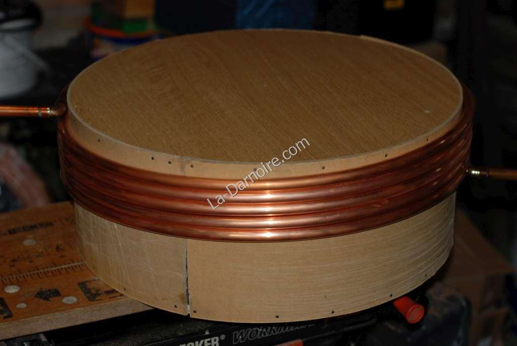 Copper tube being coiled around wooden former